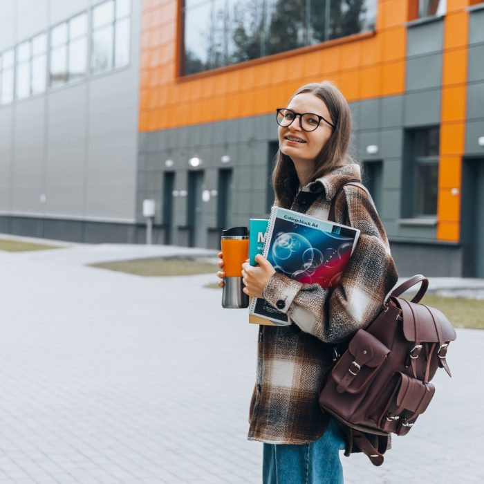 millennial-caucasian-female-student-in-glasses-and-dental-braces-with-books-walking-on-campus-after_t20_6YGaOp